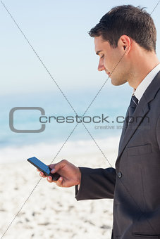 Concentrated businessman sending a text message