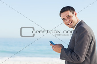 Cheerful businessman sending a text message