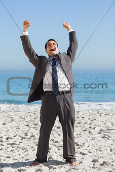 Victorious businessman in suit holding arms up