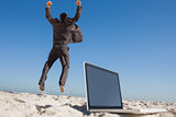 Victorious businessman jumping leaving his laptop