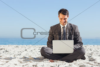 Young businessman with legs crossed typing on his laptop