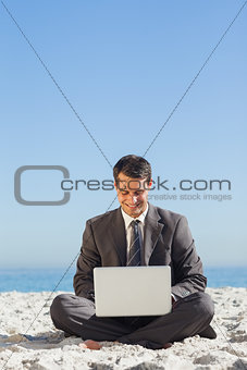 Young businessman with legs crossed with his laptop