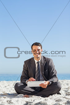 Smiling young businessman using his tablet computer