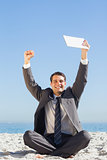 Victorious young businessman holding up his tablet computer