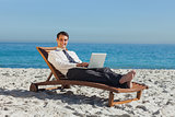 Smiling young businessman lying on a deck chair with his laptop