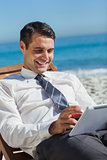 Young businessman on a deck chair using his tablet