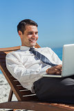 Young businessman on a deck chair using his computer