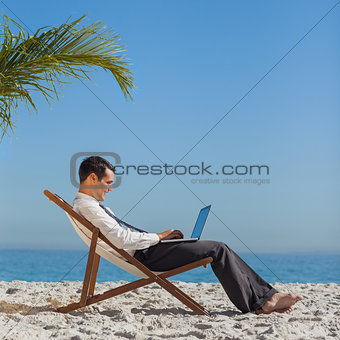 Young businessman on his beach chair using his laptop