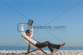 Victorious young businessman resting on his deck chair holding his tablet