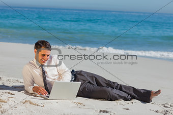 Cheerful young businessman lying on the sand with his laptop