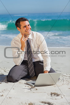 Thoughtful businessman sitting on the sand with his laptop