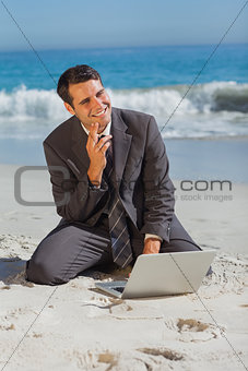 Smiling businessman sitting on the sand with his laptop