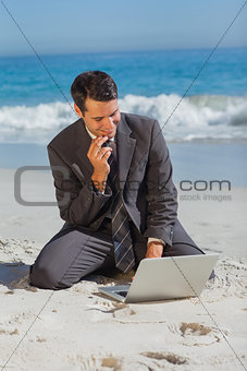 Young businessman sitting on the sand with his laptop