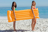 Two pretty friends holding air mattress