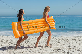 Two pretty friends running holding air mattress