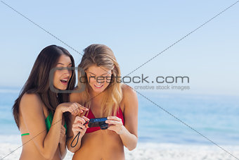 Two attractive friends looking at the pictures they just took