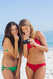 Two sexy friends looking at the pictures they just took