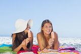 Smiling pretty women lying on their beach towel