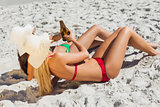 Attractive women in bikinis lying on the sand clinking glass bottles