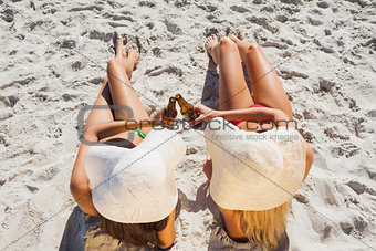Sexy blonde and brunette wearing straw hat clinking their glass bottle