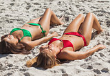 Relaxed sexy brunette and blonde taking sun