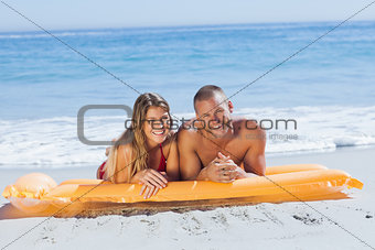 Smiling cute couple in swimsuit taking sun