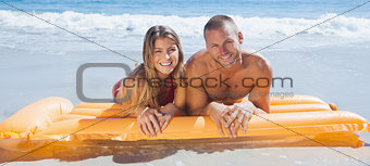 Happy cute couple in swimsuit lying on the beach