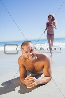 Smiling man lying on the sand while woman running to him