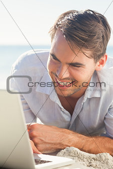 Cheerful handsome man on the beach with his laptop
