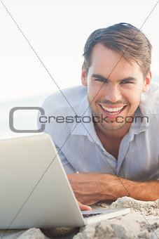 Happy handsome man on the beach with his laptop