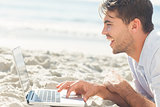 Happy handsome man on the beach using his laptop