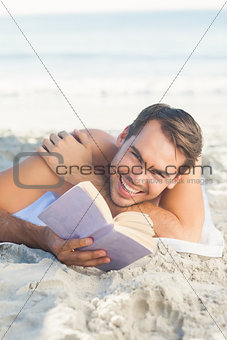 Smiling handsome man on the beach reading a book