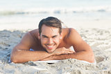 Smiling handsome man on the beach lying on his towel