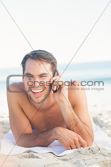 Smiling handsome man on the beach having a phone call