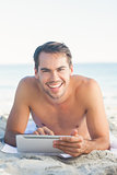 Smiling handsome man lying on his towel using his tablet