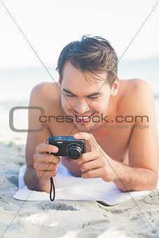 Smiling handsome man lying on his towel looking at his camera