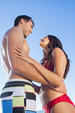 Cheerful cute couple in swimsuit holding each other