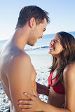 Cheerful cute couple in swimsuit holding one another