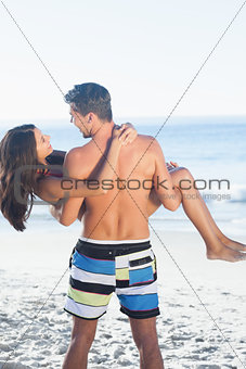 Handsome man carrying his girlfriend in his arms