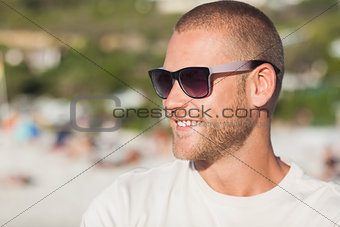 Handsome young man wearing sunglasses looking away