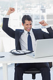 Businessman cheering and looking at his laptop