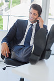Businessman on the phone relaxing with his feet on his desk