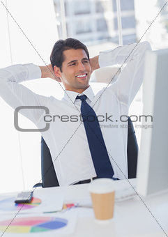 Smiling businessman relaxing on his swivel chair