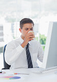Young businessman drinking coffee at his desk