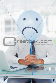 Blue balloon with sad face hiding businessmans face