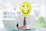 Yellow balloon with happy face hiding businessmans face