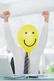 Yellow balloon with happy face hiding cheerful businessmans face