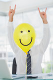 Yellow balloon with cheerful face hiding rock and roll businessman
