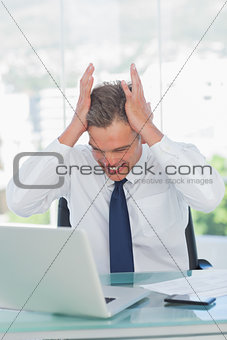 Angry businessman hands on his head looking at his laptop