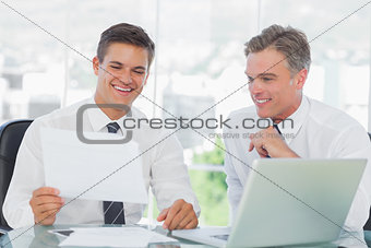 Smiling businessman listening to his intern while explaining documents